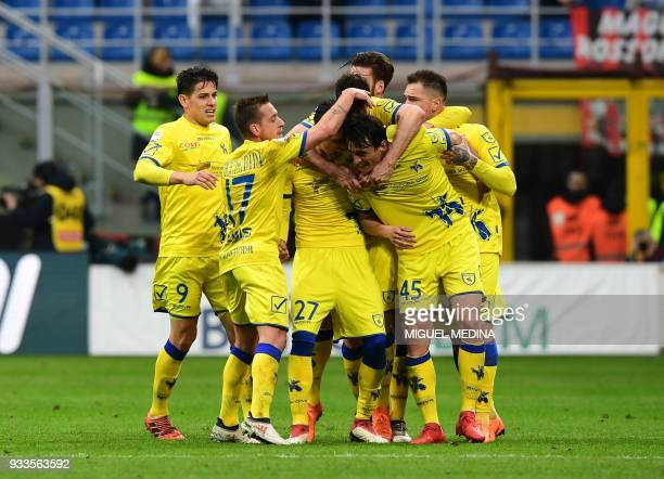 Chievo's Italian forward Roberto Inglese is congratulated by teammates after scoring during the Italian Serie A football match AC Milan vs AC Chievo...