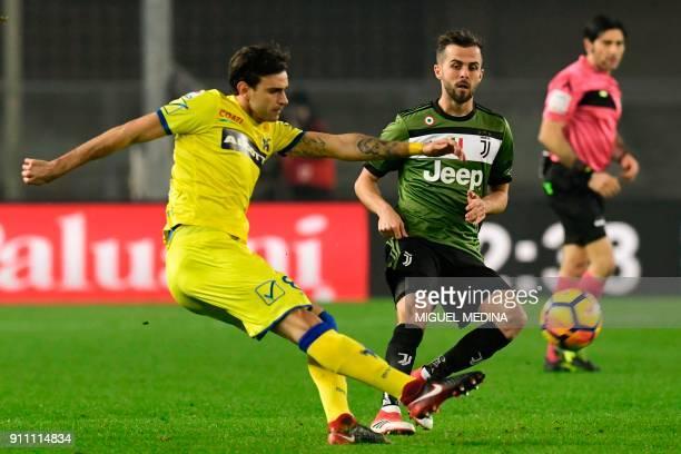 Chievo's Serbian midfielder Ivan Radovanovic kicks the ball despite Juventus' Bosnian midfielder Miralem Pjanic during the Italian Serie A football...