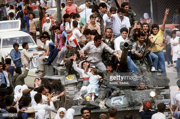 Chi'ite Muslim inhabitants of Tyre southern Lebanon sitting atop of a tank belonging to the Amal Shia militia celebrate 29 April 1985 in Tyre partial...