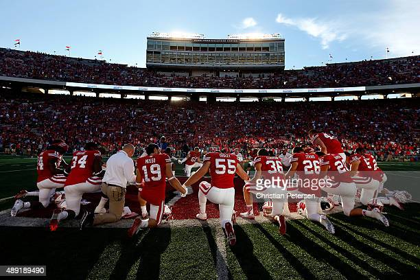 Chikwe Obasih, Leo Musso#19, Garret Dooley, Joe Ferguson, Derek Straus and Austin Ramesh of the Wisconsin Badgers huddle up with teammates at...