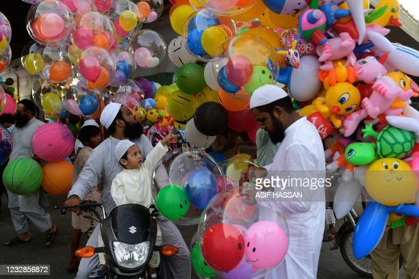 Child accompanying his parents buy baloons after offering special prayers on the occasion of Eid al-Fitr that marks the end of the holy month of...