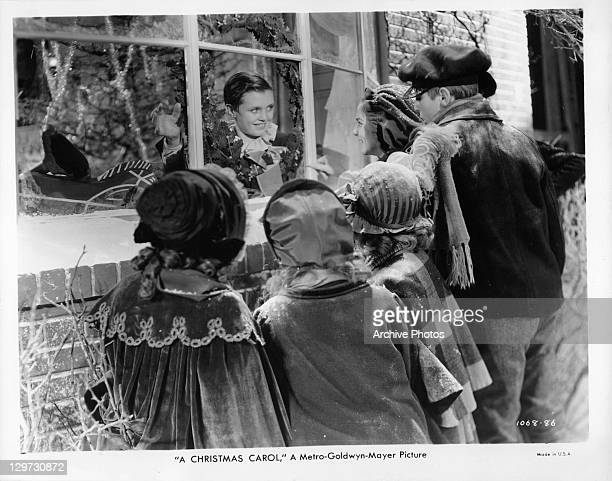 Child actor Terry Kilburn waving at carolers in a scene from the film 'A Christmas Carol' 1938