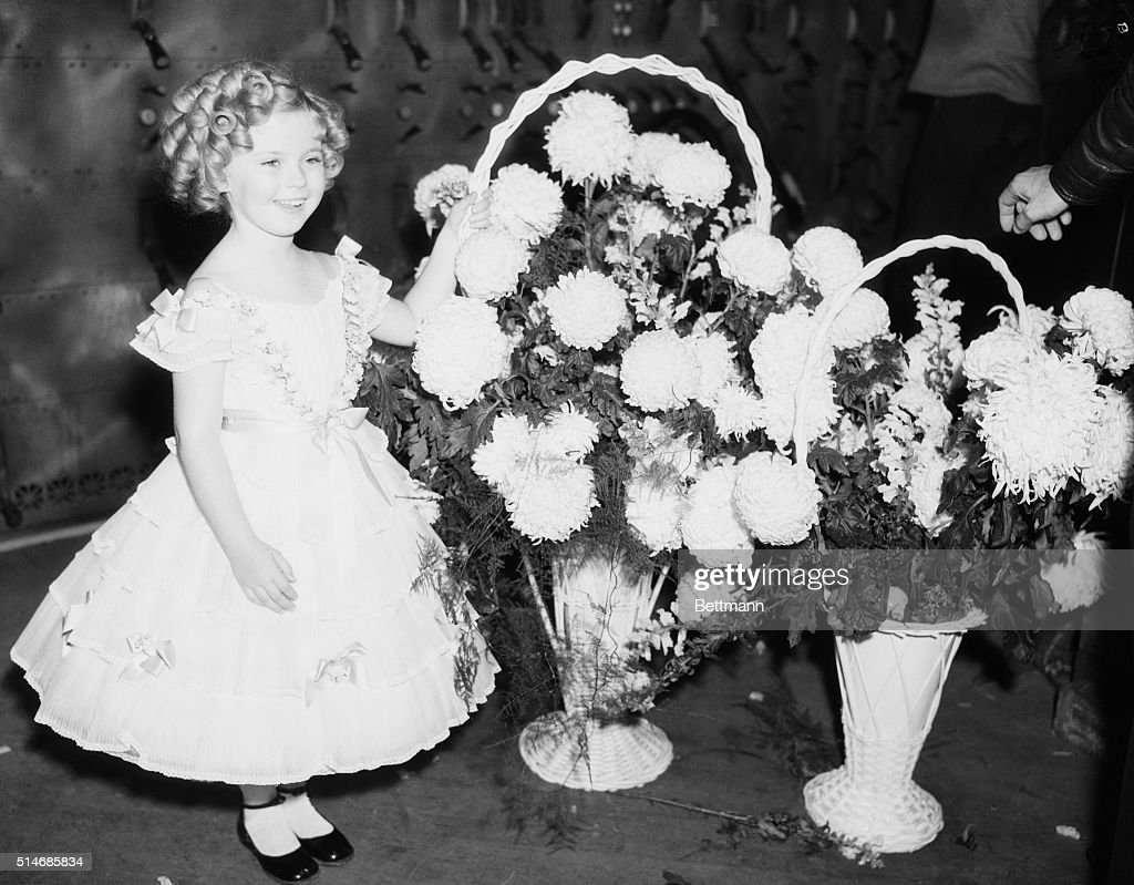 Child actress Shirley Temple stands with baskets of flowers on December 3, 1935. She is backstage during the Will Rogers Memorial 'Show of Shows'. This was a fundraiser to create a permanent memorial to Rogers.