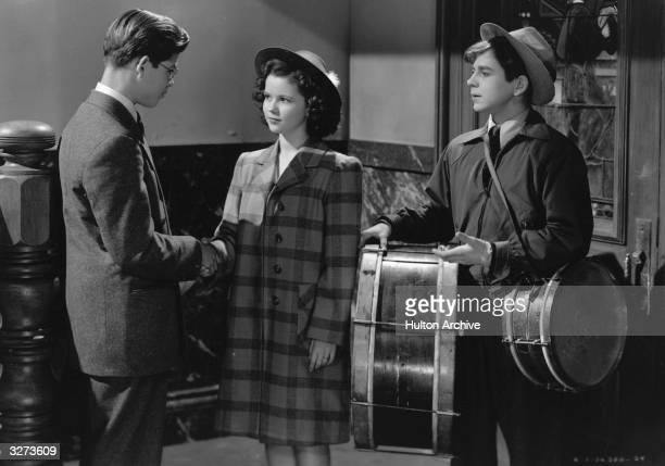 Child actress Shirley Temple stars with Dickie Moore and Roland DuPree who is holding a set of drums in a scene from the film 'Miss Annie Rooney' the...