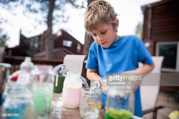 child adding chemicals to an experiment - potion stock photos and pictures