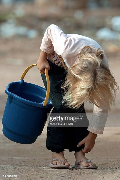 A child adjusts her pants as she searches for water in Porto Alegre Brazil 02 February 2002 Una nina se entretiene mientras se dirige a buscar agua...