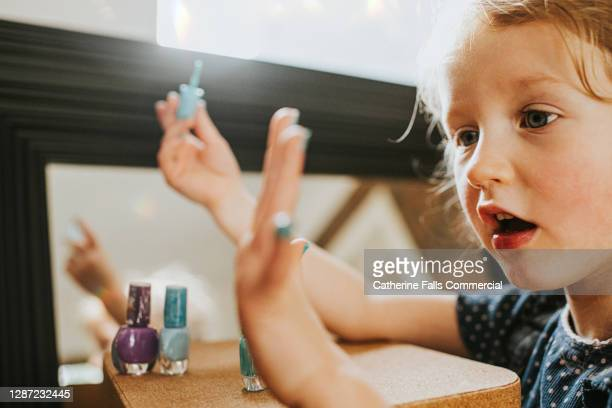 child admiring her freshly painted finger nails - human finger stock pictures, royalty-free photos & images