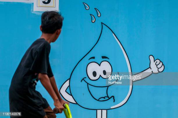 A child affected by a disaster passes in front of a water mural in the Duyu Temporary Shelter complex Palu Central Sulawesi Indonesia Saturday March...