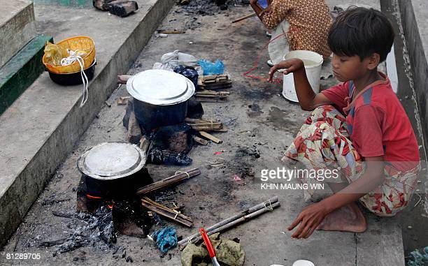 A child affected by cyclone Nargis keeps an eye on cooking food in Dala on the outskirts of Yangon on May 17 2008 State television on May 17 2008 put...
