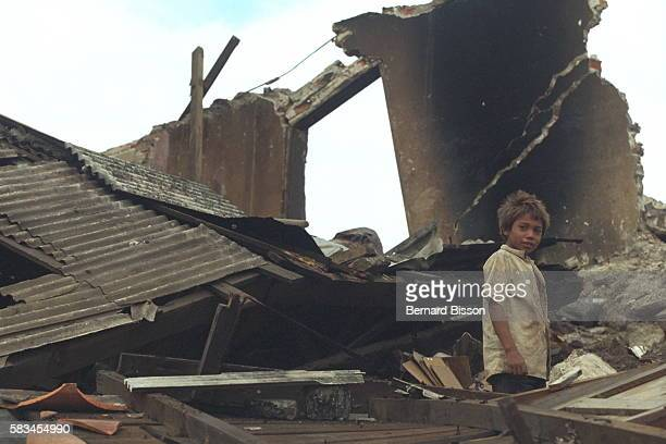 Child among the ruins of a burnt-out house.