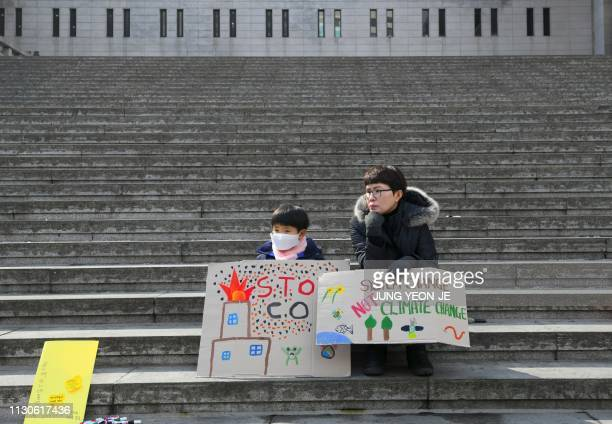 TOPSHOT A child and a woman attend a rally supporting a global strike by students against climate change in Seoul on March 15 2019 Thousands of young...