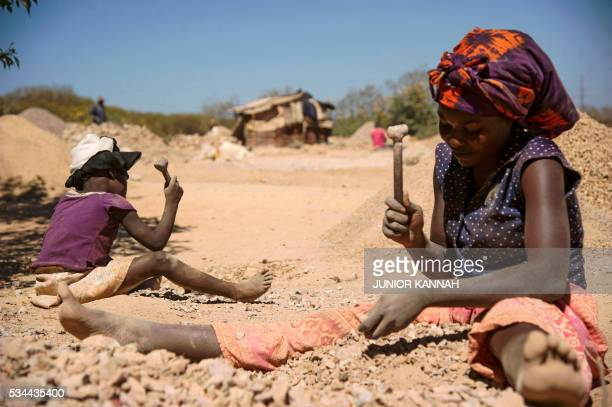 Child and a woman break rocks extracted from a cobalt mine at a copper quarry and cobalt pit in Lubumbashi on May 23, 2016. The price of copper has...