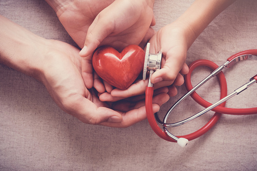 child and adult holding red heart with stethoscope, heart health,  health insurance concept 953685706