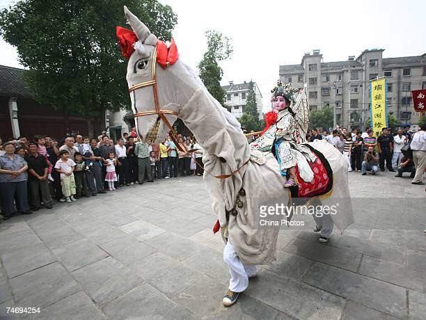 A child and adults acting as a horse perform the 'Tiaowuchang' Dance during a ceremony to mark the upcoming Duanwu Festival on June 17 2007 in...