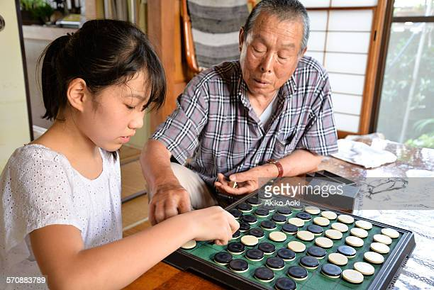 Child and aged man playing Othello game.