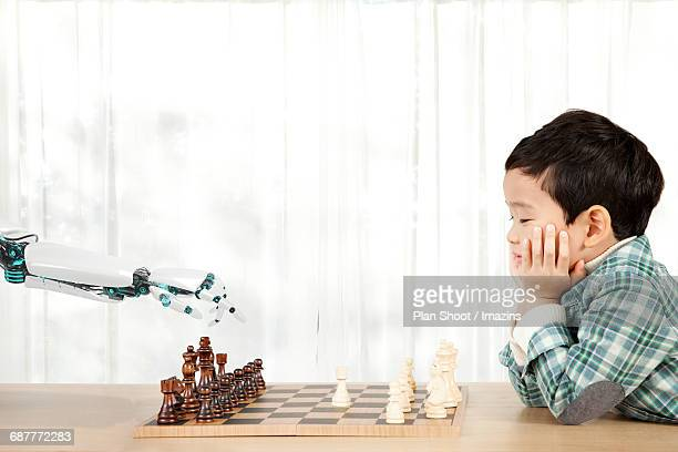 A child and AI robot arm playing chess
