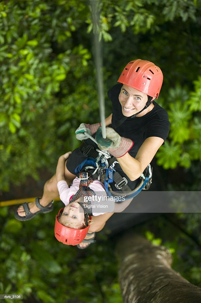 Child and an adult suspended on a rope in the forest : Foto de stock
