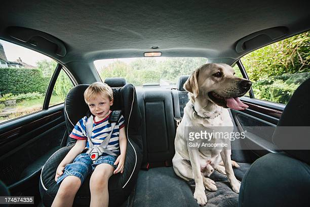 Child and dog sat in a car