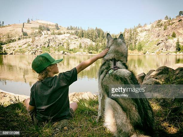 Child and dog sit at a mountain lake in summer
