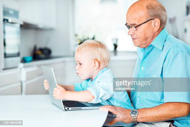 Child and grandfather are bonding while playing with laptop