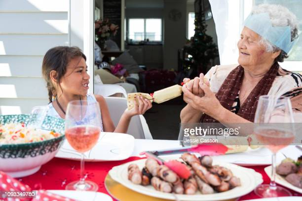 Child and grandma pull a Christmas cracker at lunch table