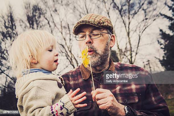 Child and Grandpa playing with toy windmill