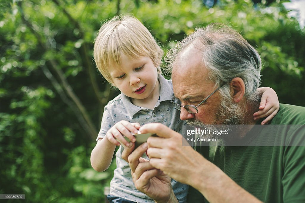 Child and Grandparent using a smart phone : Stock Photo