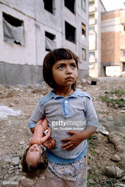 A child and her doll on a poor housing estate in a Tirana suburb The country opened up after the death of Stalinist leader Enver Hoxha in 1985...