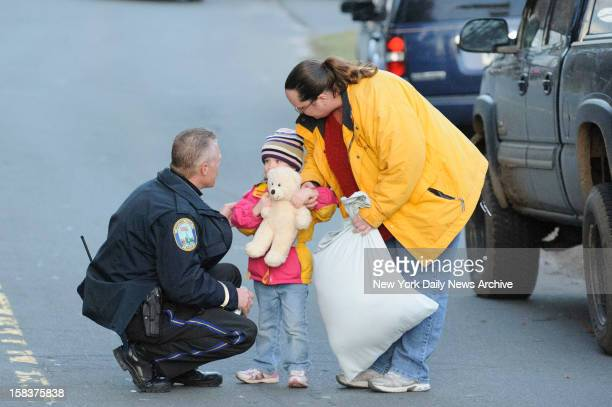 A child and her mother leave staging area outside Sandy Hook Elementary School in Newtown CT A gunman opened fire inside school killing 27 people...