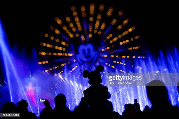 ANAHEIM CA ––FEBRUARY 02 2011––A child and his Mickey Mouse ears are silohuetted against the World of Color nightly light and water show at Disney...
