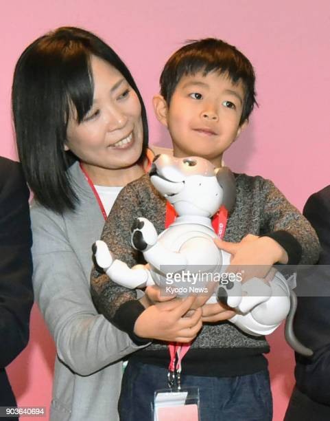 A child and his mother pose for a photo with their Aibo robot dog at the headquarters of Sony Corp in Tokyo on Jan 11 2018 Sony delivered the first...