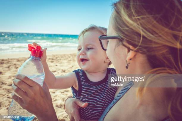 child and his mother with bottled water on the beach - hot mom stock photos and pictures