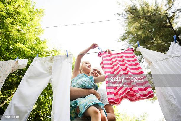 Child and Man Hanging Laundry in the Backyard