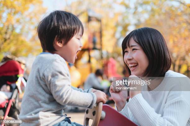 child and mother playing in park - japan mom and son stock photos and pictures