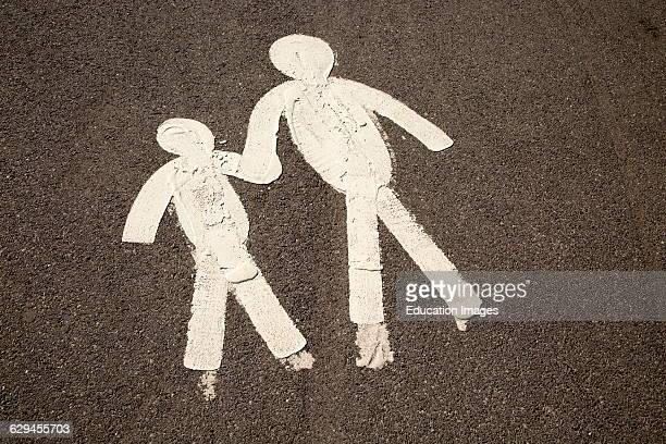 Child and parent figures holding hands on tarmac pavement Mumbles South Wales UK