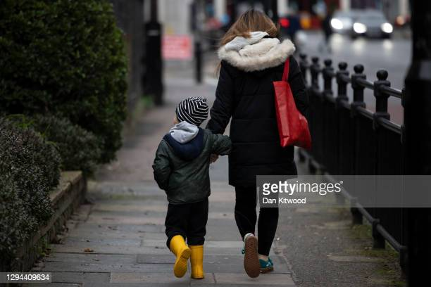 Child and parent walk near a closed primary school in Deptford on January 04, 2021 in London, England. Primary schools across London and southeast...