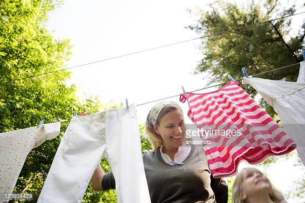 Child and Woman Hanging Laundry in Back Yard lifestyle