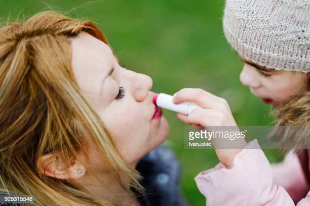 Kind einen Lippenbalsam auf ihre Mutter Lippen auftragen