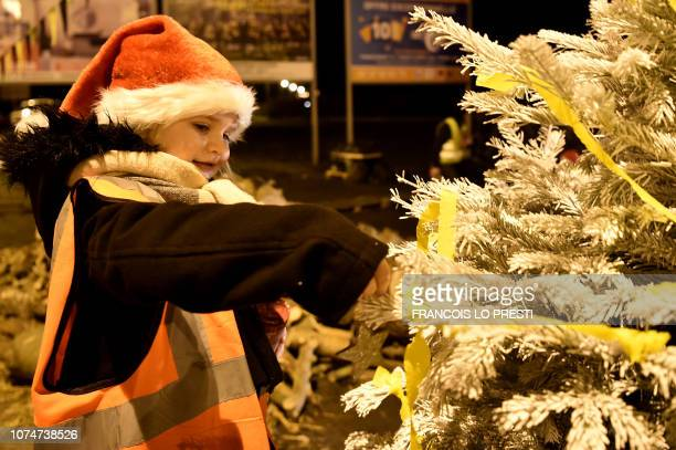 A child arranges a Christmas tree as yellow vests protestors spend Christmas eve on a roundabout in Somain northern France on December 24 2018 French...