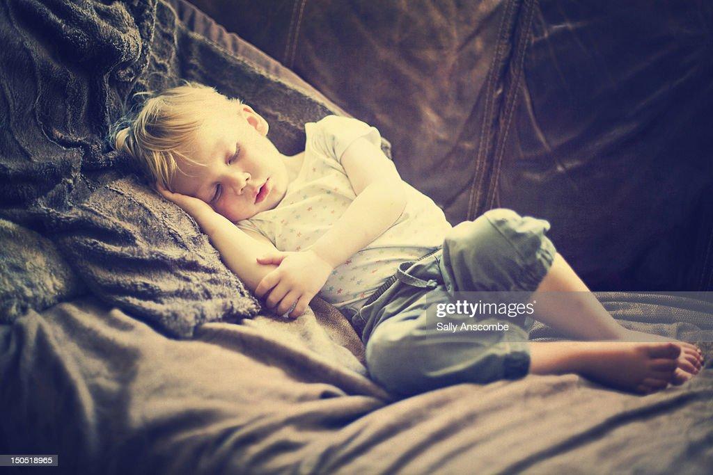 Child asleep on sofa : Stock Photo