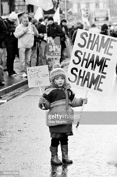 Child at a Budget Protest in Dublin holding placards.