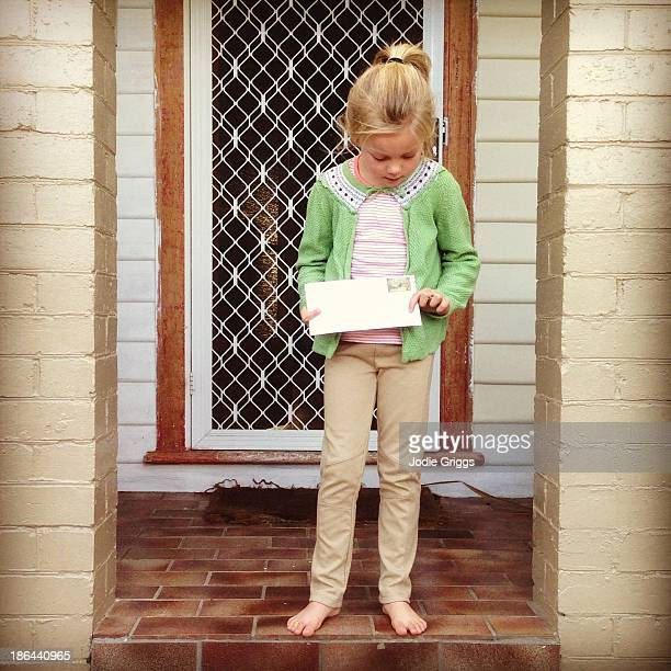 Child at front door of house holding a letter