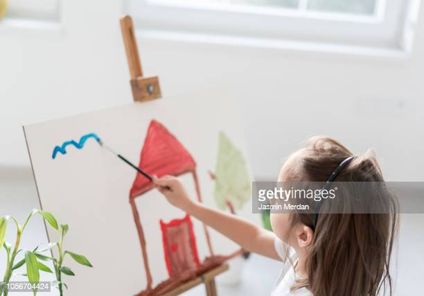child at home painting on canvas at home - drawing activity stock pictures, royalty-free photos & images