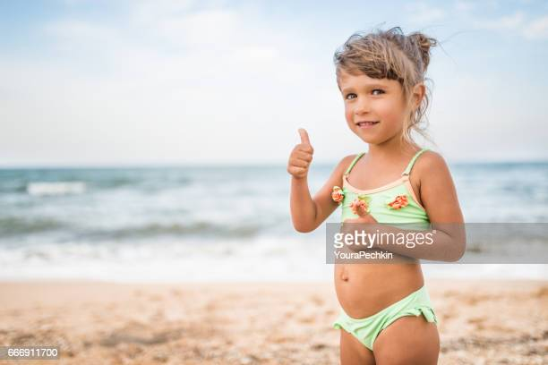 Child at sea shore showing thumbs up sign