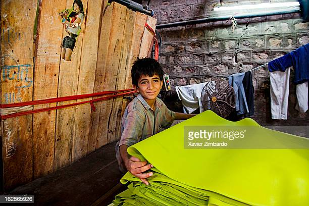 Child at work while raw cloth undergoes dyeing process at colour dyeing machine on April 1 2009 in Rajasthan India