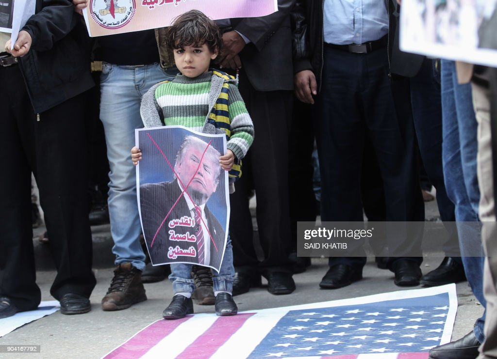 A child attends a protest by Palestinian supporters of the Islamic Jihad movement against the US president's decision to recognise Jerusalem as the capital of Israel, in the town of Rafah in the southern Gaza Strip, on January 12, 2018. /