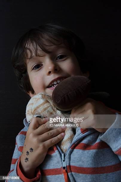 Child babywearing two stuffed animals.