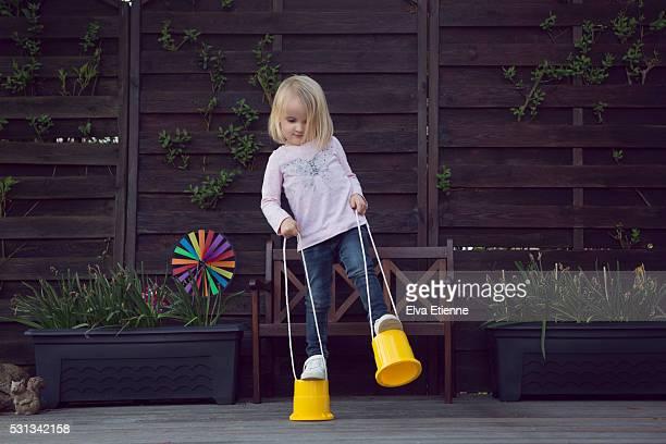 Child (3-4) balancing on stilts