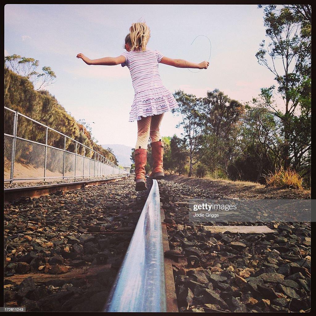 Child balancing & walking along railway line alone : Stock Photo