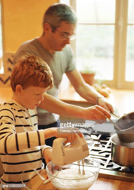 Child beating  egg whites, man holding saucepan